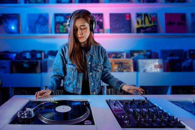 Joven mujer dj latina mezclando msica en una tienda de discos de vinilo