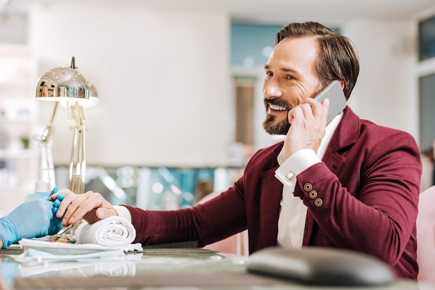 Uomo maturo gioviale che ha conversazione sul telefono e che sorride
