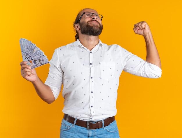 Un bell'uomo adulto gioioso con gli occhiali che tiene i soldi facendo un gesto di sì con gli occhi chiusi isolati sul muro arancione