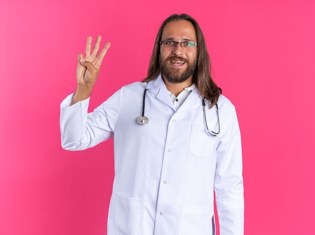Gioioso medico maschio adulto che indossa accappatoio medico e stetoscopio con occhiali guardando la telecamera che mostra tre con la mano isolata sulla parete rosa