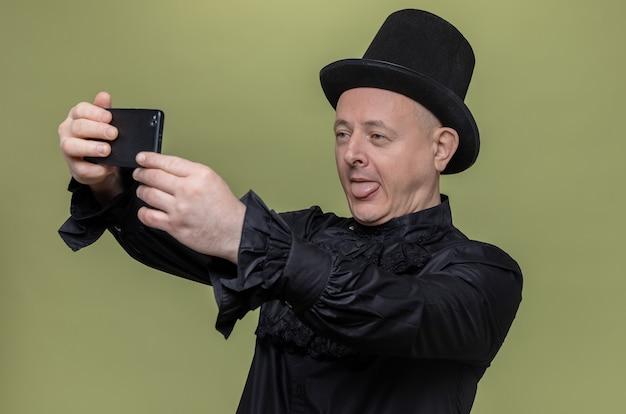 Uomo slavo adulto gioioso con cappello a cilindro in camicia gotica nera che prende selfie