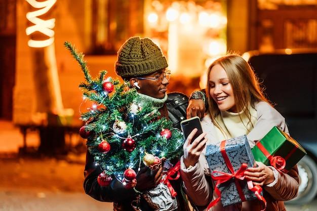 Gioioso uomo afroamericano con donna caucasica all'aperto facendo regali di natale online