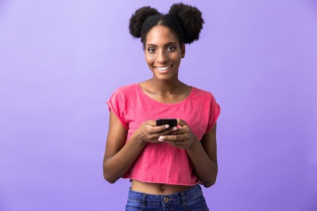 Gioiosa donna afro-americana sorridente e tenendo il telefono cellulare, isolato