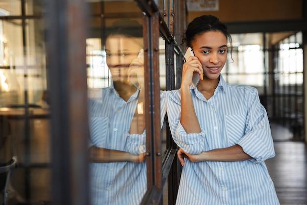 Gioiosa donna afroamericana che parla al cellulare e sorride mentre si appoggia alla parete di vetro in un ufficio moderno