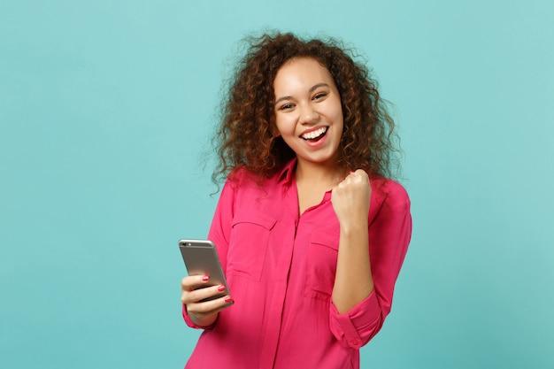 Gioiosa ragazza africana in abiti casual facendo gesto vincitore utilizzando il telefono cellulare, digitando un messaggio sms isolato su sfondo blu turchese. persone sincere emozioni, concetto di stile di vita. mock up copia spazio.