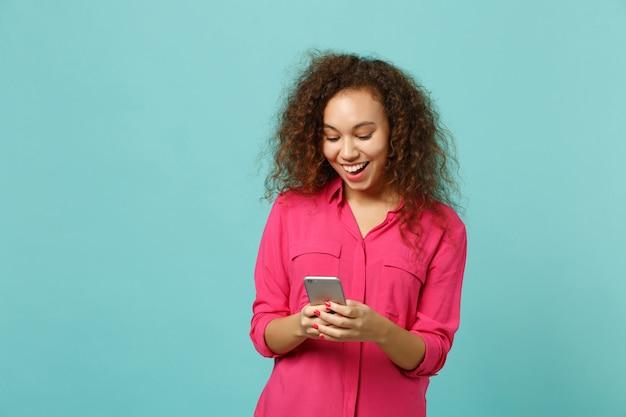 Gioiosa ragazza africana in abiti casual rosa utilizzando il telefono cellulare, digitando un messaggio sms isolato su sfondo blu turchese parete in studio. persone sincere emozioni, concetto di stile di vita. mock up copia spazio.