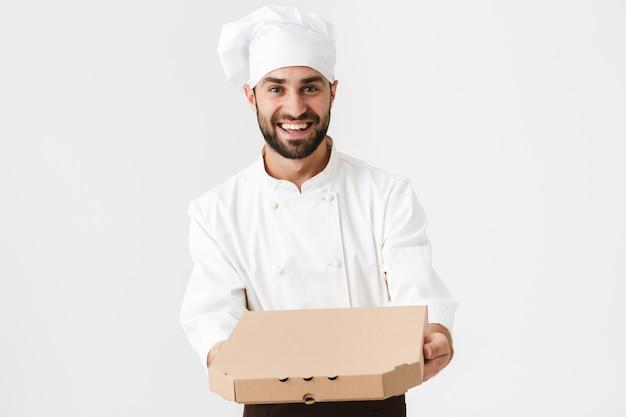 Gioioso fornaio in uniforme da cuoco che sorride e tiene in mano una scatola per pizza isolata su un muro bianco