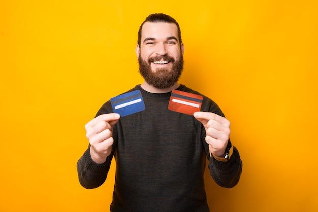 Uomo bello barbuto gioioso che mostra due carte di credito