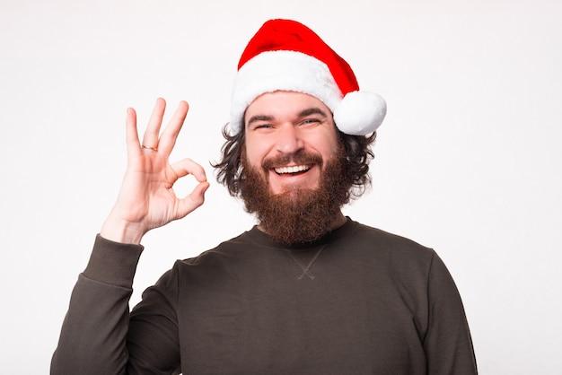 Uomo barbuto allegro che sorride e che mostra gesto giusto