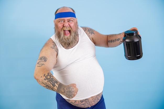 Un gioioso uomo barbuto con sovrappeso tiene in mano una bottiglia nera di integratore proteico su sfondo azzurro