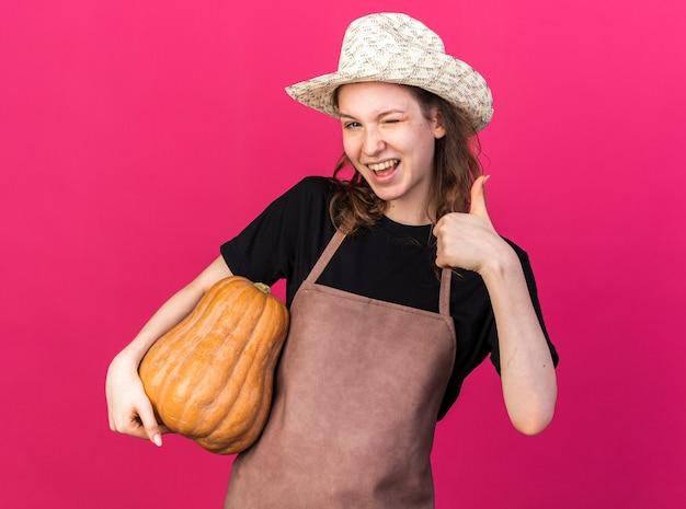 Gioiosa giovane giardiniera femmina sbatté le palpebre che indossa un cappello da giardinaggio che tiene in mano una zucca che mostra il pollice in su