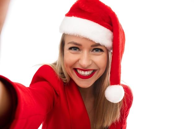 Signora bionda allegra in vestito rosso e cappello della santa che tiene la sua mano mentre prende un selfie. concetto di vacanza