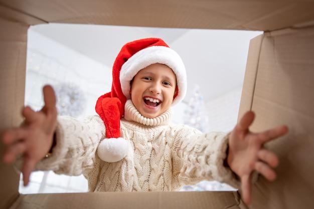 Un ragazzo gioioso con un maglione leggero e un cappello di babbo natale tira fuori un regalo dalla scatola allungando le mani verso il regalo. guarda e guarda il bambino felice. regalo di natale