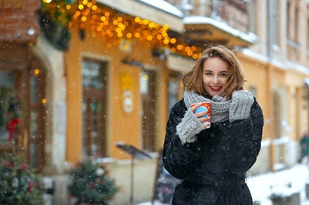 La gioiosa donna bruna indossa una sciarpa lavorata a maglia e un cappotto caldo beve caffè in strada durante la nevicata. spazio per il testo