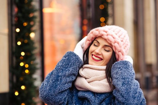 Una gioiosa donna castana indossa un berretto rosa chiaro lavorato a maglia e una sciarpa che cammina per la città decorata con ghirlande. spazio per il testo