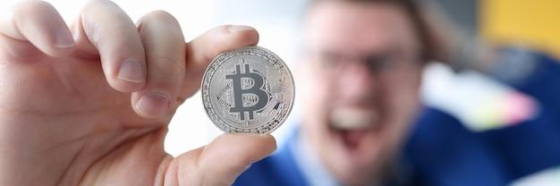 Uomo d'affari allegro che tiene moneta con guadagni del logo bitcoin sul concetto di criptovaluta