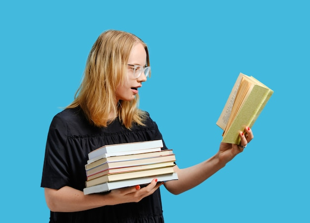 Gioioso studente caucasico con libri in mano.