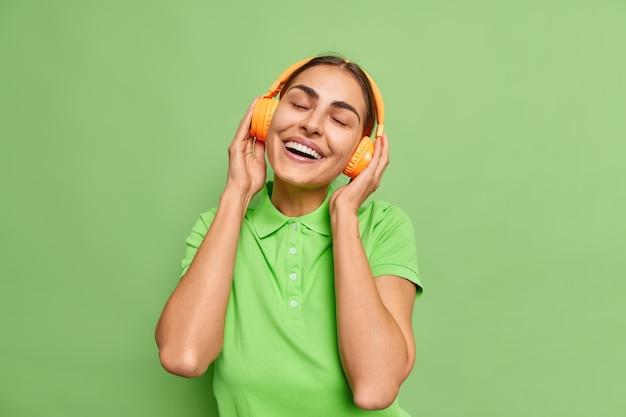 La gioiosa donna caucasica gode della melodia preferita della canzone agghiacciante in cuffie wireless inclina la testa sorride ampiamente tiene gli occhi chiusi vestito con una maglietta casual isolata sul muro verde