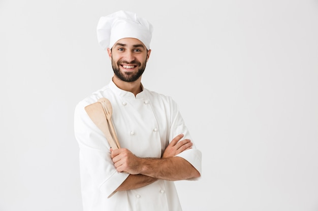 Gioioso capo uomo in uniforme da cuoco che sorride mentre tiene in mano utensili da cucina in legno isolati su un muro bianco