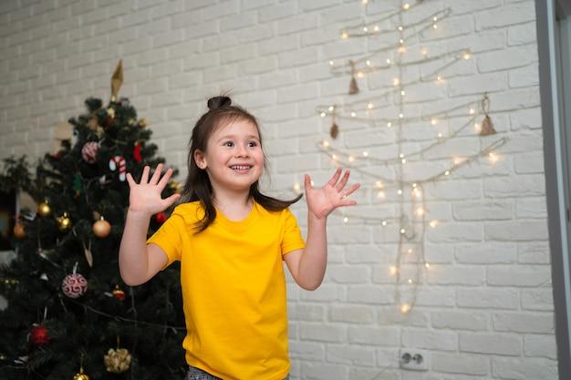 Un bambino gioioso cattura orpelli. una luminosa vacanza per bambini. un bambino con una maglietta gialla cattura una serpentina.