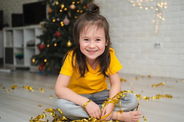Un bambino gioioso cattura orpelli. una luminosa vacanza per bambini. un bambino con una maglietta gialla cattura una serpentina