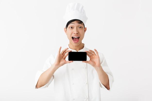 Gioioso capo uomo cinese in uniforme bianca da cuoco e cappello da cuoco che tiene il telefono cellulare isolato sopra il muro bianco