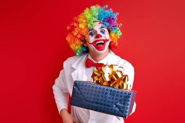 Il pagliaccio gioioso fa esibizioni per gli ospiti, regala una confezione regalo. isolato su sfondo rosso