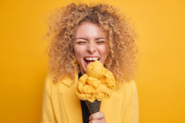 La donna riccia allegra si diverte a tenere la bocca aperta morsi freddi il delizioso gelato sembra sciocchezze divertenti in giro durante le vacanze estive isolate sul muro giallo. mangiare un buon gelato porta gioia