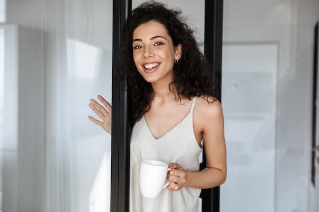 Gioiosa donna riccia con lunghi capelli scuri che indossa abiti per il tempo libero sorridendo e guardando te, mentre in piedi vicino alla porta di vetro a casa con una tazza di tè