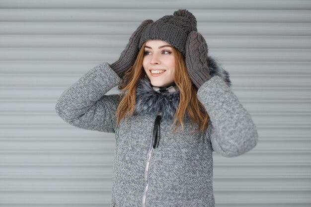 Gioiosa giovane donna carina in un cappello lavorato a maglia grigio in un elegante cappotto grigio con pelliccia in guanti vintage lavorati a maglia con un bel sorriso vicino al muro bianco di metallo. la ragazza felice gode del fine settimana.