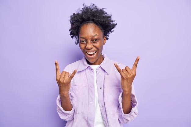 Adolescente gioiosa dalla pelle scura con i capelli ricci di pelle scura fa il gesto delle corna e gode della musica rock