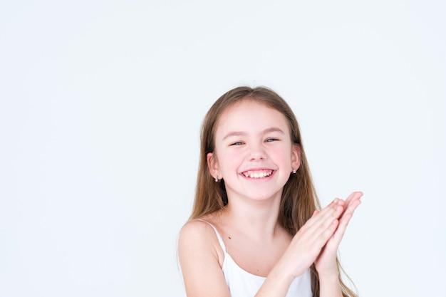Gioioso bambino felice battendo le mani sul muro bianco.