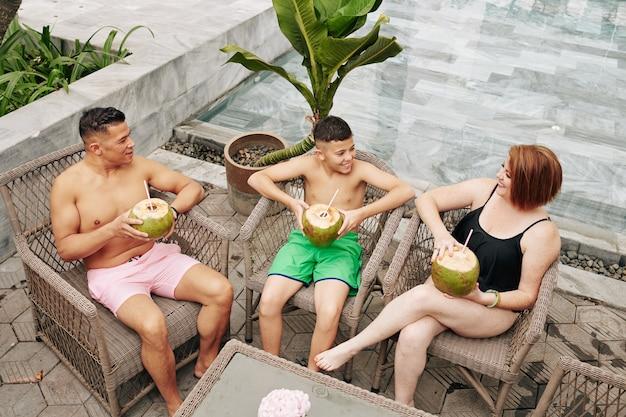 Famiglia gioiosa seduta su sedie in rattan dopo aver nuotato in piscina, bevuto cocktail di cocco e discusso di vacanze
