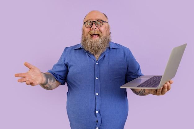 L'uomo d'affari grasso allegro in camicia attillata con gli occhiali tiene il computer portatile su fondo porpora