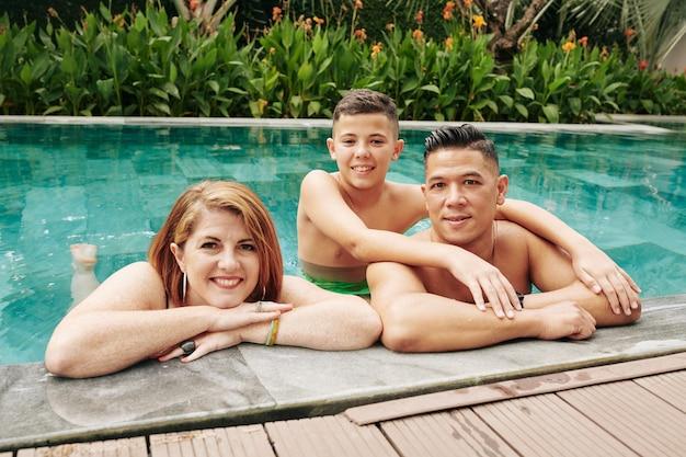Padre, madre e figlio gioiosi in piedi in piscina e sorridono alla telecamera