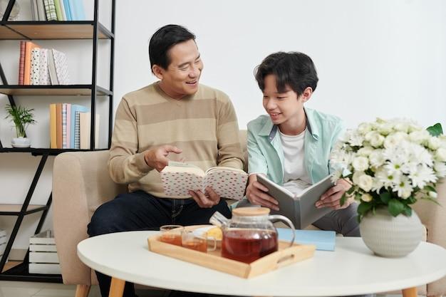 Padre gioioso e figlio adolescente che leggono e discutono libri con romanzi interessanti a casa quando bevono il tè
