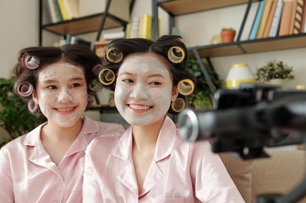 Gioiose blogger femminili che si filmano mentre applicano maschere di argilla che riducono al minimo i pori che provano