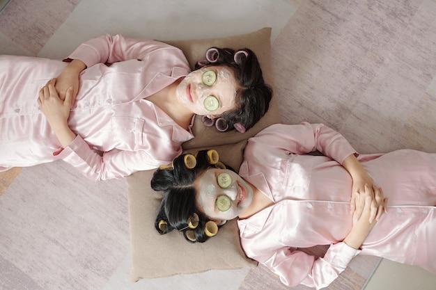 Amiche gioiose che si rilassano con una maschera di argilla purificante e fette di cetriolo sul viso vista dall'alto