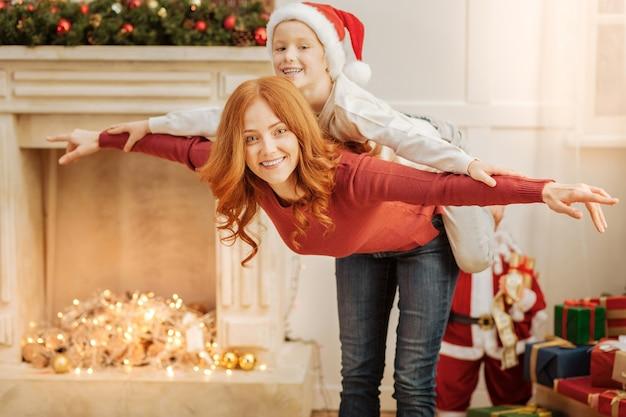 Genitore femminile gioioso e il suo adorabile figlio sorridono allegramente divertendosi e fingendo di volare a casa.