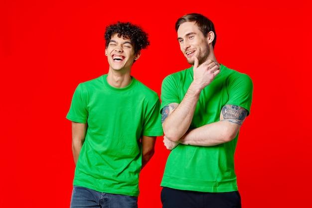 Amici allegri in magliette verdi sono in piedi accanto a uno sfondo rosso