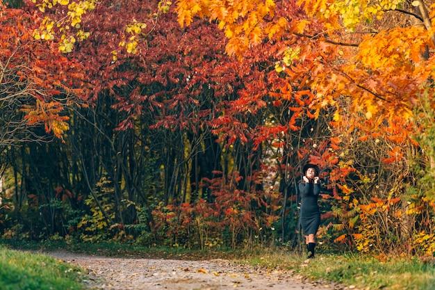 La ragazza allegra in un vestito verde tocca un cappello dalle sue mani e guarda le cime degli alberi nella foresta