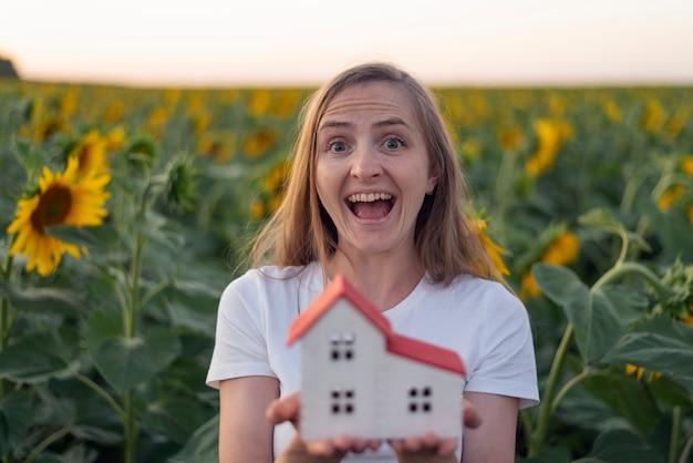 Ragazza allegra tiene sulle sue palme modello di casa, sfondo di girasoli. case ecologiche. serre.