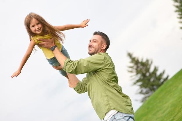Ragazza gioiosa che gioca con suo papà nel parco verde allungando le mani fingendo di volare