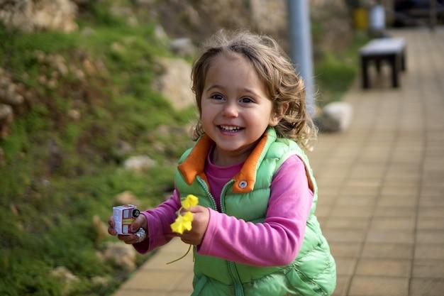Ragazza allegra che corre nel parco con un fiore e un giocattolo nelle sue mani