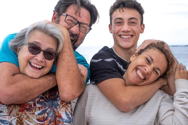 Un gioioso gruppo di madri e figli, diverse generazioni della stessa famiglia, si divertono all'aria aperta in riva al mare. da adolescente a nonna