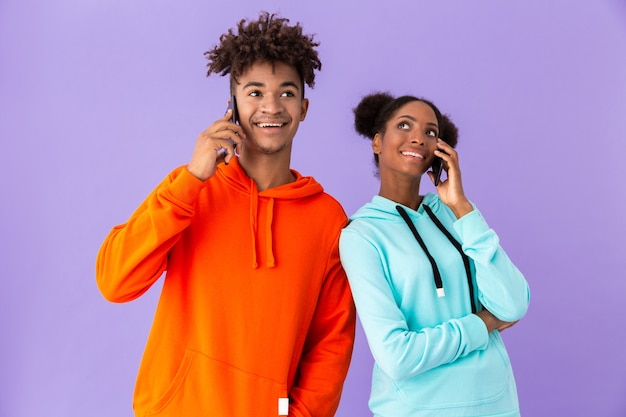Ragazzo allegro e ragazza che parlano insieme sul telefono cellulare, isolato sopra la parete viola