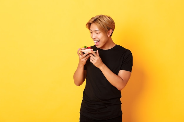 Ragazzo asiatico bello allegro che sorride e che guarda tentato alla torta mentre fa il morso
