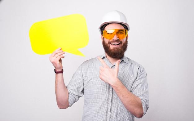 Gioioso bello architetto barbuto uomo che indossa il casco protettivo e punta al fumetto giallo