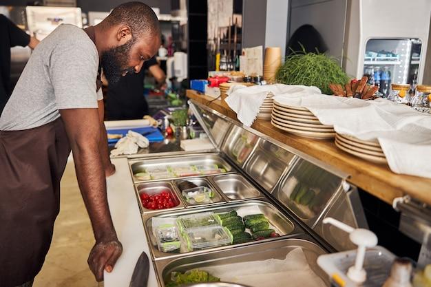 Lo chef barbuto bello e gioioso è in piedi al tavolo con le verdure tagliate per fare la pizza al ristorante