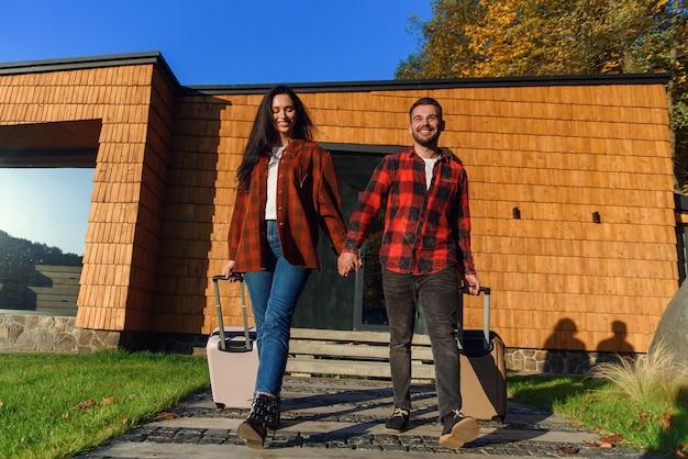 Gioioso bel giovane barbuto e donna abbastanza elegante che esce dalla casa moderna con le valigie mentre vanno insieme al viaggio di vacanza.